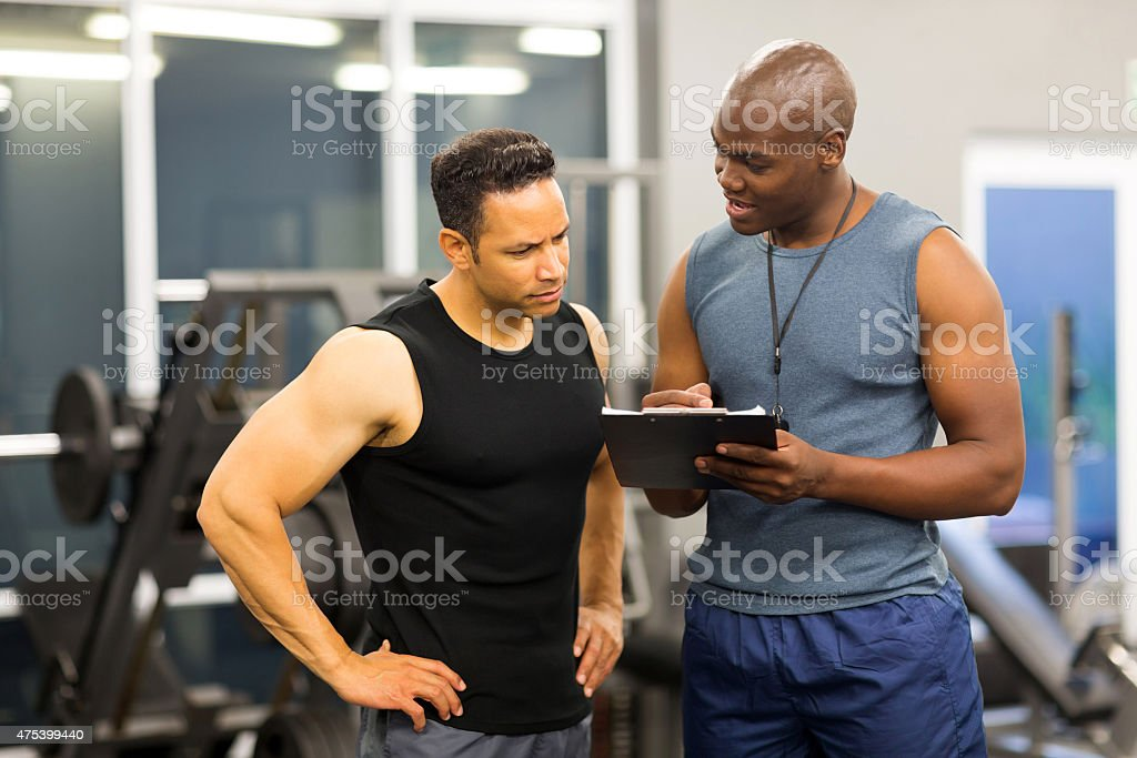 african personal trainer helping man to fill the membership form stock photo