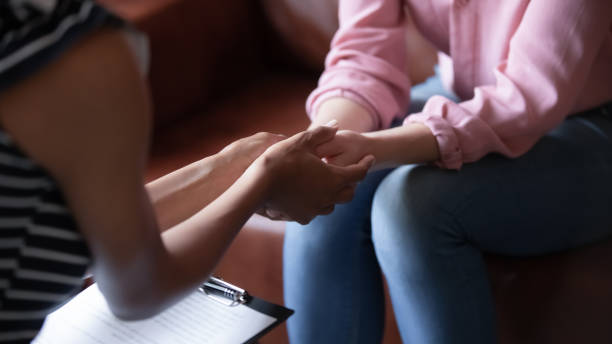African psychologist holds hands of girl patient, closeup view stock photo