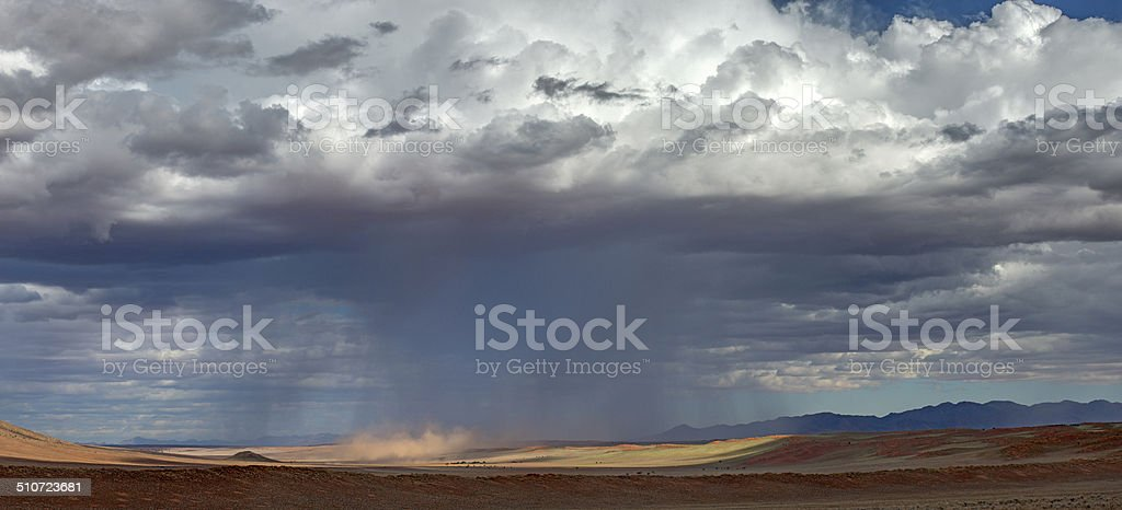 A rare rain storm falls over the Namibian landscape and sand dunes at...