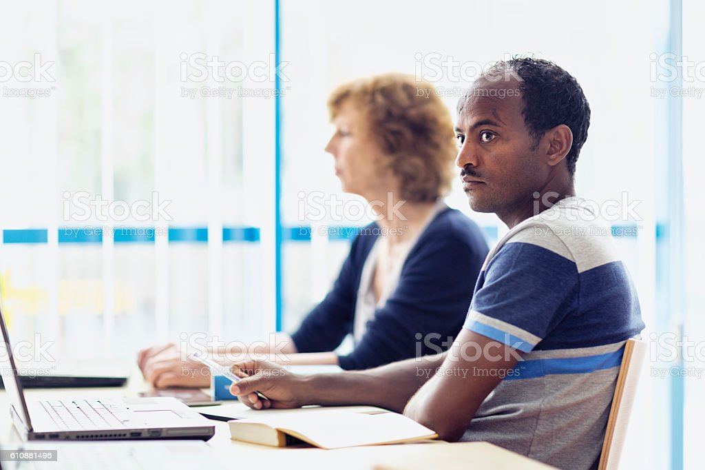 african refugee learning language in computer lab stock photo