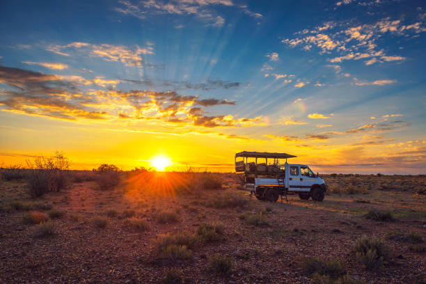 African safari vehicle stops in the Kalahari desert for dramatic sunset stock photo