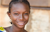 Gorgeous young girl from Mali proudly smiles while looking at the camera in the public school of Bamako.