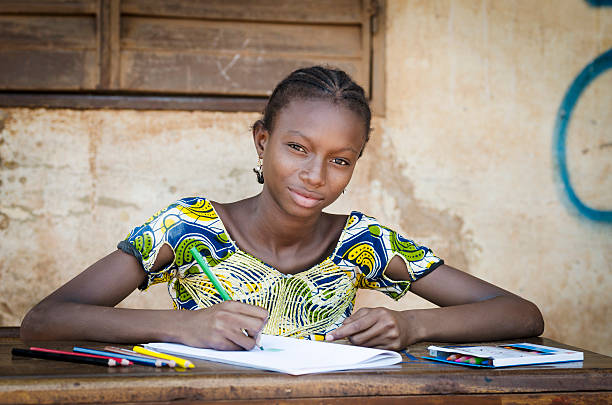 African School Girl Posing for an Educational Shot Symbol Portrait of an African ethnicity schoolgirl (age 13) in an educational environment in Bamako, Mali learning her lesson outdoors sitting on a desk and slightly smiling. developing countries stock pictures, royalty-free photos & images