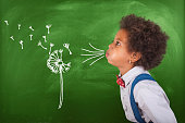 African schoolgirl blowing dandelion seeds