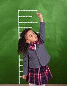 istock African schoolgirl is showing height on a blackboard scale 1268084699