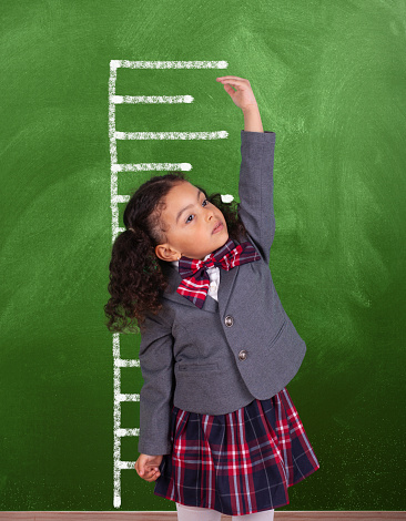 African schoolgirl is showing height on a blackboard scale