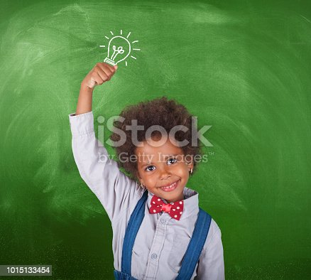 African schoolgirl with a light bulb in front blackboard