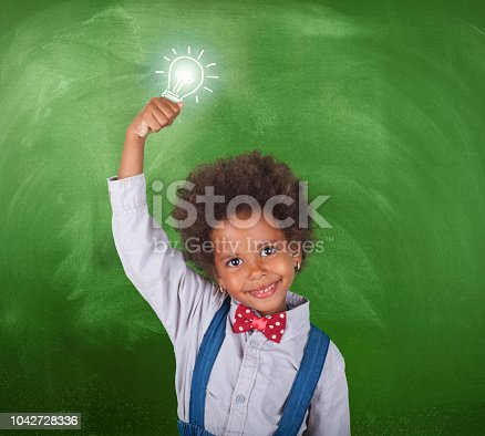 480585411 istock photo African schoolgirl with a light bulb in front blackboard 1042728336