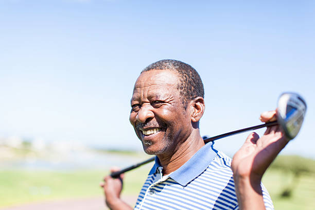 African senior golfer holding his club with a smile. African senior golfer holding his club with a smile at Langebaans golf course in Western Cape, South Africa. 65 69 years stock pictures, royalty-free photos & images