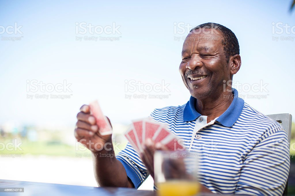 African senior playing a game of cards stock photo