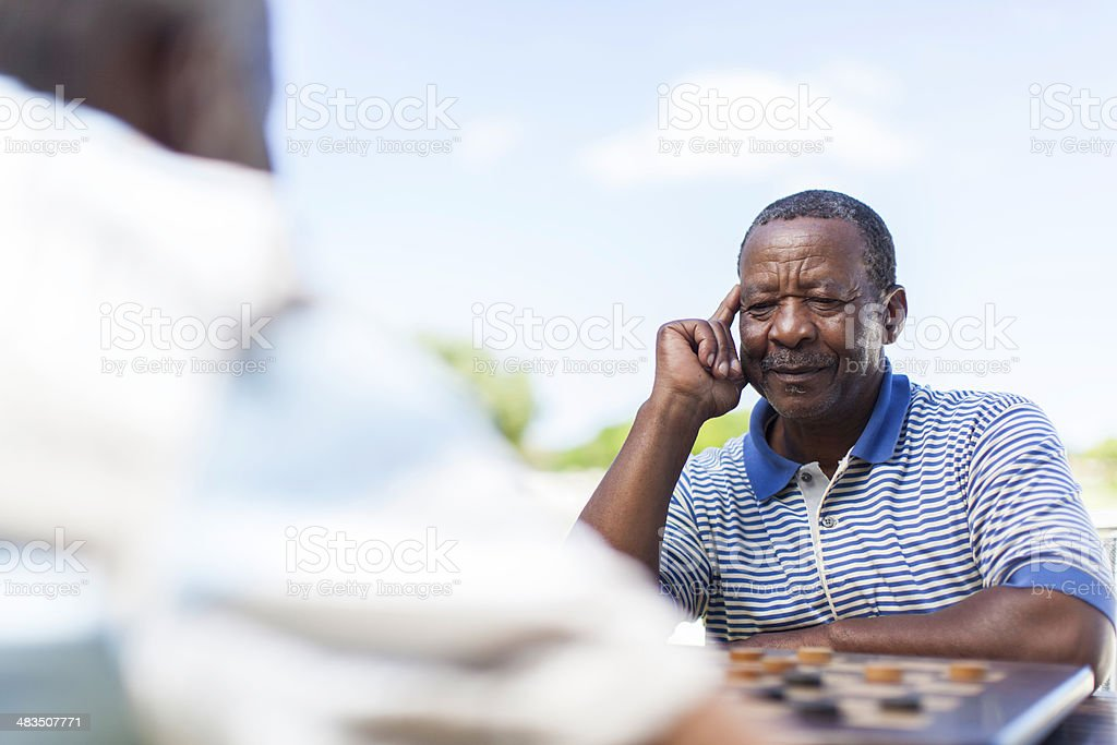 African senior thinking about his next move stock photo