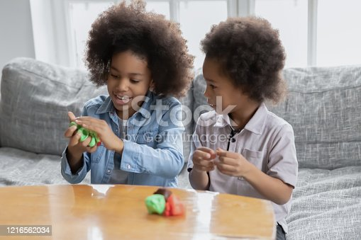 African siblings sit on couch spend time using play dough making diverse shapes have fun together at home, older sister teach younger brother to create. Hobby pastime useful activities for kid concept