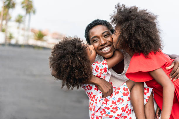African sisters twins kissing mother on the beach - Black family having fun outdoor during summer vacation - Love, real people and travel concept - Main focus on mum face stock photo