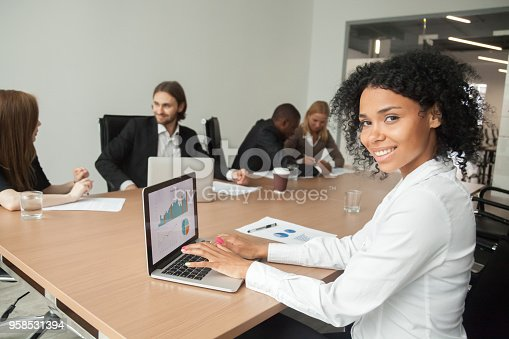 istock African smiling businesswoman looking at camera using laptop at meeting 958531394