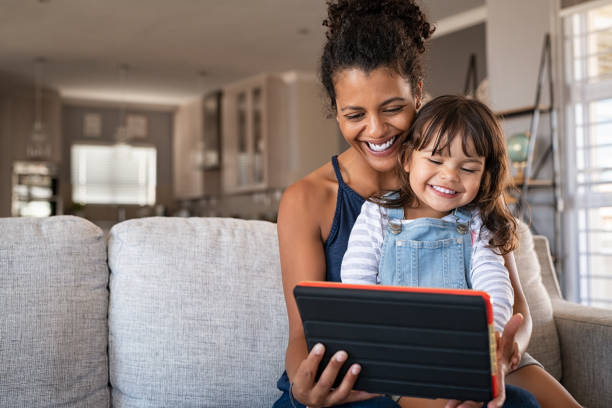 African smiling mother and happy daughter using digital tablet stock photo