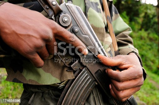 An African soldier grips a Kalashnikov type semi-automatic assault rifle.