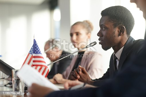 Side view of African businessman performing during conference he sitting at the table and speaking into the microphone