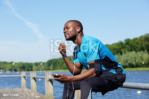598157464 istock photo African sports man sitting outside listening to music 484712436