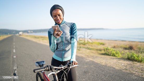 African sportswoman with hijab, with a bike using smart phone on road