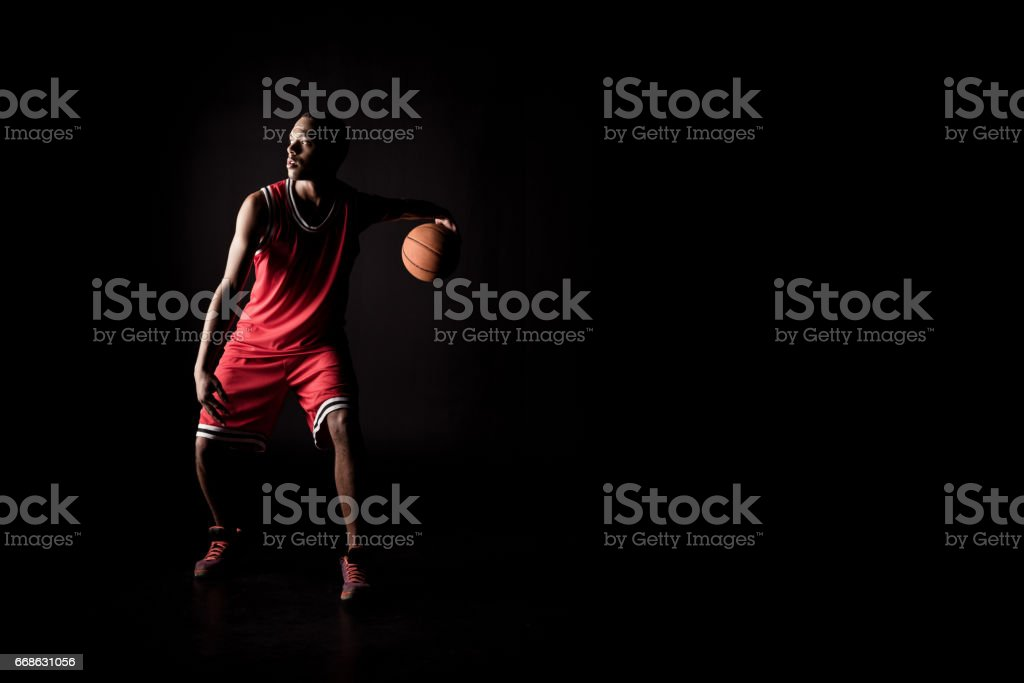 african sporty man in sports uniform playing basketball on black stok fotoğrafı