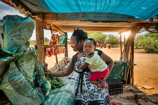 african street vendor, mother holding her child between the bags of tomatoes and cabbage