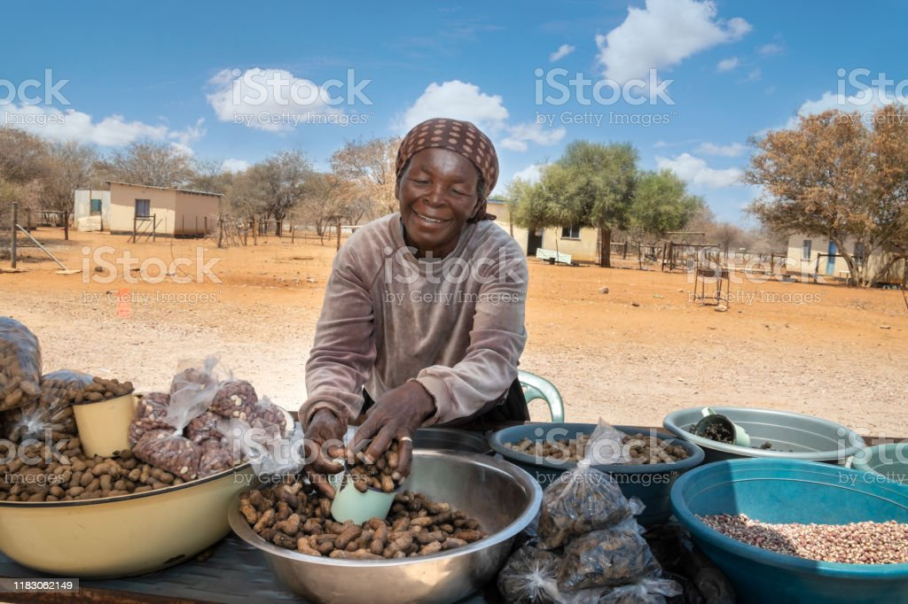 African street vendors on the road selling raw peanuts African street vendors on the road selling raw peanuts, corn, monkey oranges and mopane worms, Africa Stock Photo