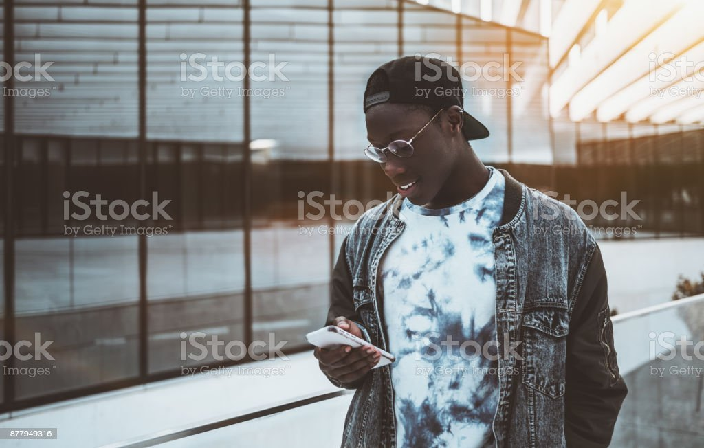 African student messaging via his smartphone stock photo