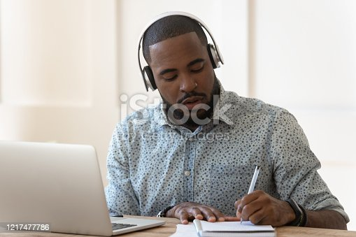Focused african student sit at desk wearing wireless headphones learning preparing for seminar or exam, guy interpreter hears audio writing down translation, online lecture course e-learning concept