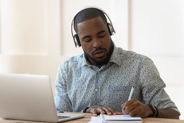 African student wearing headphones listens audio course makes notes Focused african student sit at desk wearing wireless headphones learning preparing for seminar or exam, guy interpreter hears audio writing down translation, online lecture course e-learning concept adult stock pictures, royalty-free photos & images