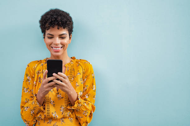 African stylish woman using smart phone Happy smiling black woman using smart phone. Young brazilian woman writing a message with mobile isolated on blue background. Portrait of african american stylish girl using cellphone with copy space. phone stock pictures, royalty-free photos & images