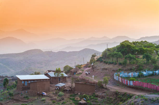 African Sunset Scene Rural village with one person walking in distance next to a red and blue fence between houses at sunset Lalibela Ethiopia Horn of Africa village stock pictures, royalty-free photos & images