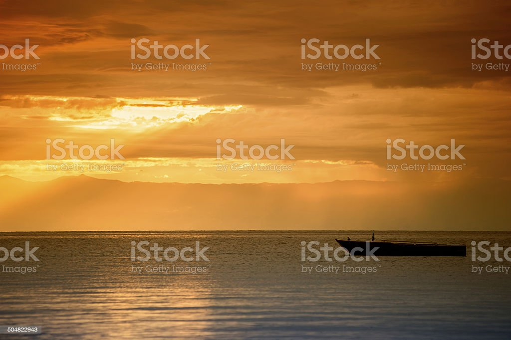 African sunset with a  typical wooden boat on Lake Tanganyika stock photo