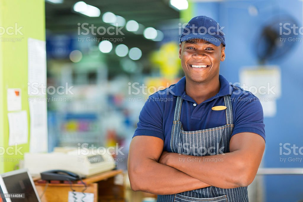 african supermarket cashier standing at checkout stock photo