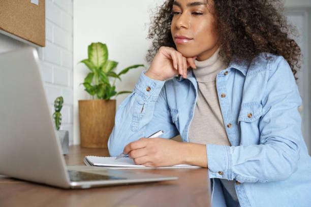 afrikaanse tiener meisje student, school leerling, remote worker studeren aan het kantoor aan huis kijken naar onderwijs opleiding webinar podcast op de computer, elearning video conferencing, het maken van notities. close-up - e learning stockfoto's en -beelden