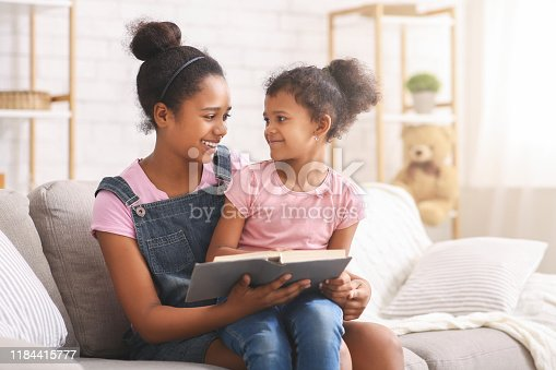 Story time. African teen sister reading book to her little sister, free space