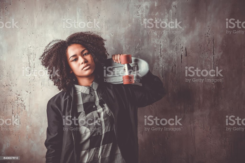 African teenager girl with skateboard in front of a concrete stock photo