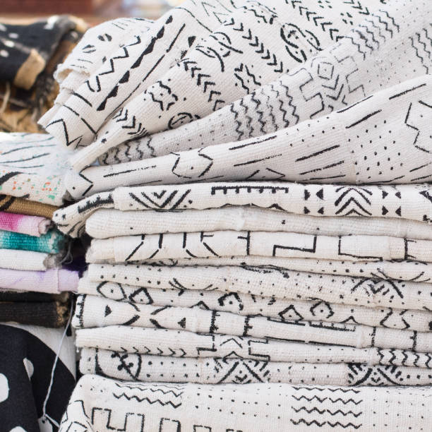 african textiles at a market stall featuring black and white patterns on hand-woven cloth by a woman from ghana - kente cloth stock photos and pictures