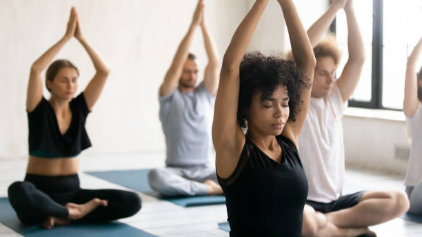 Entrenador africano y grupo de personas meditando durante la clase de yoga - foto de stock