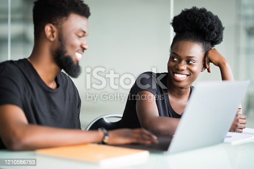 istock African two young businesspartners interacting at meeting in office 1210586753