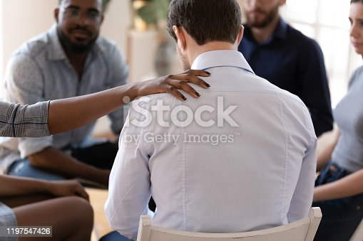 African psychologist put hand on shoulder of addicted man close up rear view supporting him, diverse people gathered at rehab group, psychological assistance drugs alcohol addiction treatment concept