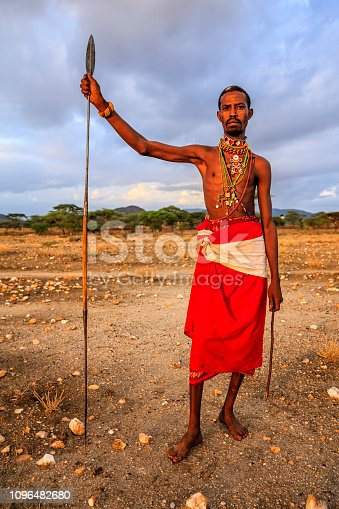 African warrior from Samburu tribe standing on savanna and holding a spear, central Kenya. Samburu tribe is one of the biggest tribes of north-central Kenya, and they are related to the Maasai.