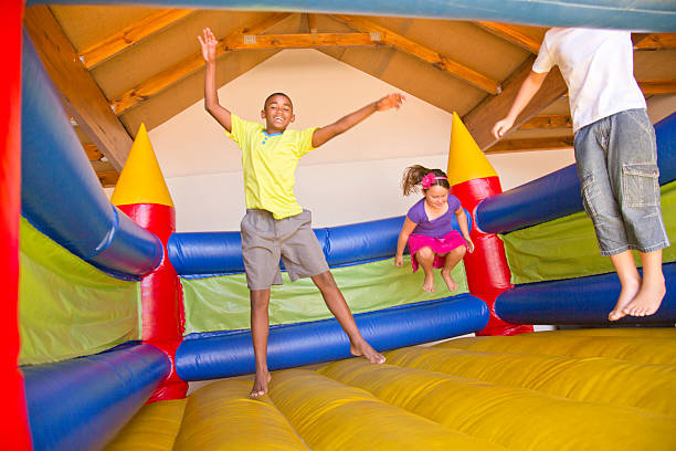 African & white children jumping on a bouncy castle stock photo