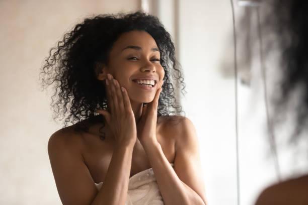 afrikaanse vrouw na douche kijken in spiegel aanraken zachte huid - mirror mask stockfoto's en -beelden