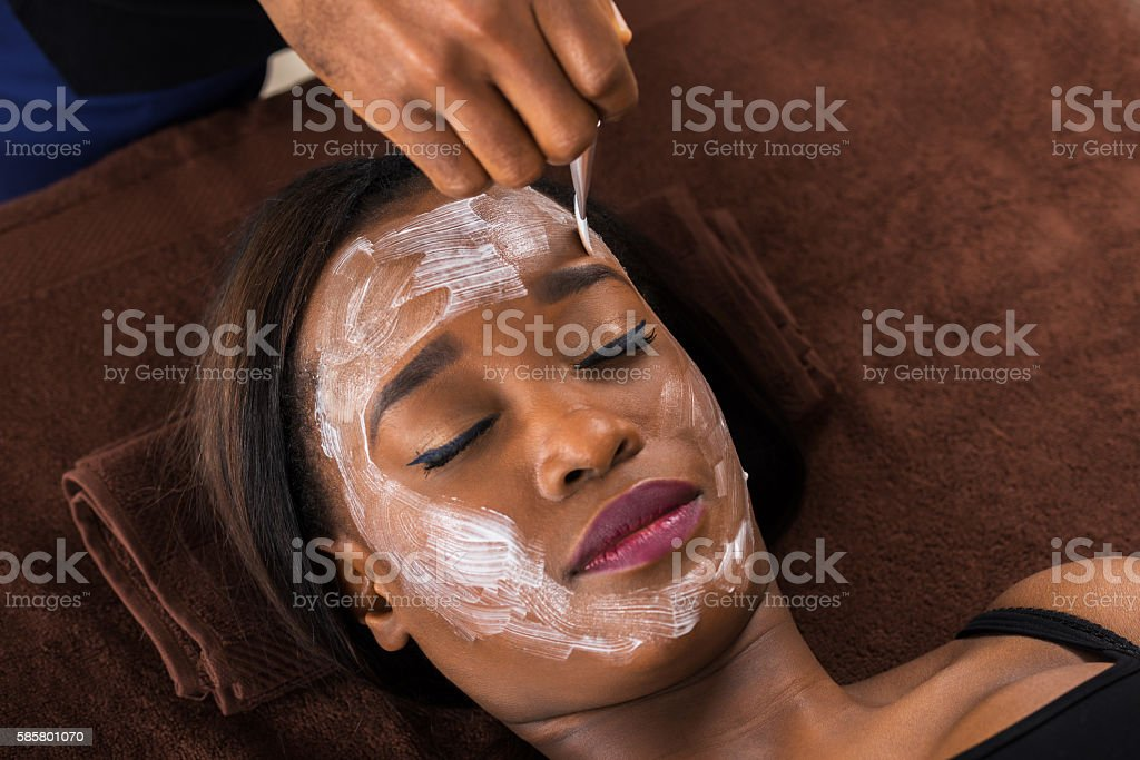 African Woman Applying Facial Mask In Spa stock photo