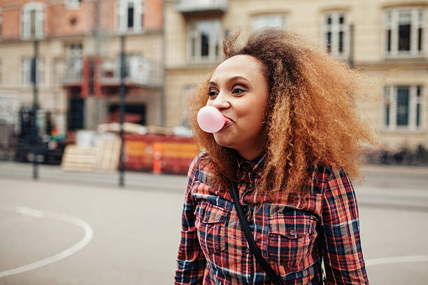 African woman blowing bubble gum stock photo