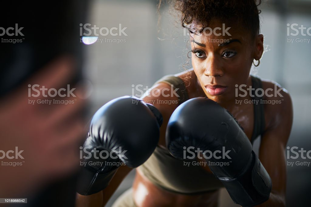 african woman boxing with punching bag in garage gym stock photo