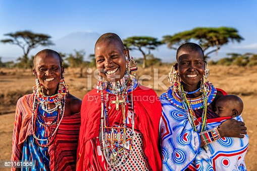 African mother from Maasai tribe carrying her baby , Kenya, Africa - Mount Kilimanjaro on the background. Maasai tribe inhabiting southern Kenya and northern Tanzania, and they are related to the Samburu.