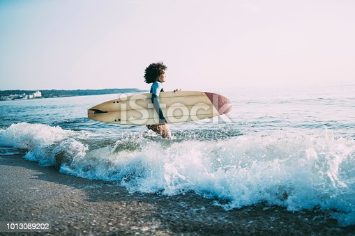 Side view of african woman with surfboard going into sea.