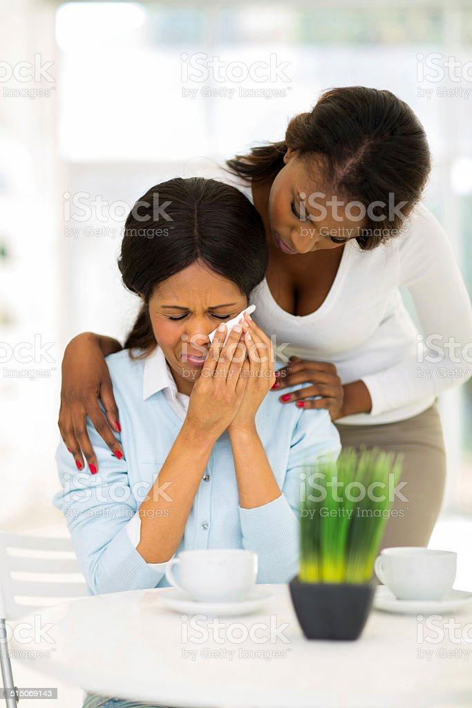 african woman comforting crying mother stock photo
