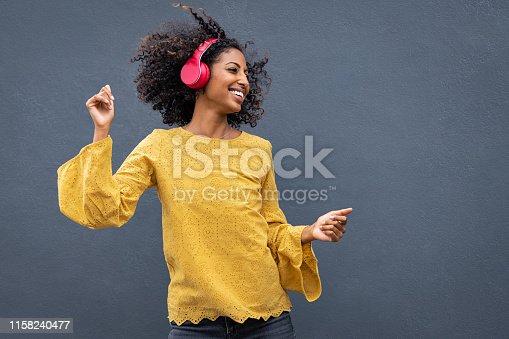 Beautiful black girl listening music in headphones from smart phone or mp3 player and dancing. Cheerful young woman with curly hair making dance moves to the rhythm of music while listening through wireless headphones isolated on grey wall.